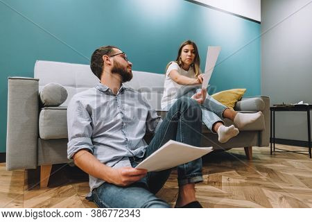 A Young Couple Manages Finances By Looking Through Their Bank Accounts In The Living Room By The Sof