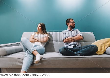 Husband And Wife Sit On The Couch After A Quarrel And Do Not Talk To Each Other. High Quality Photo