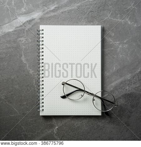 Open Notebook With Glasses On Grey Marble Table Top View, Spiral Notepad On Gray Office Desktop. Cle