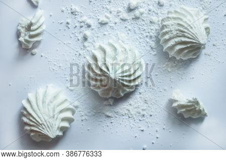 Three White Air Meringues Lie Diagonally On A White Background. Next To Them Crumbs Of Broken Mering