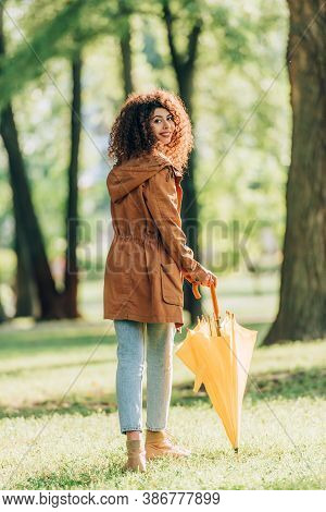 Back View Of Curly Woman In Raincoat Holding Umbrella While Looking At Camera In Park