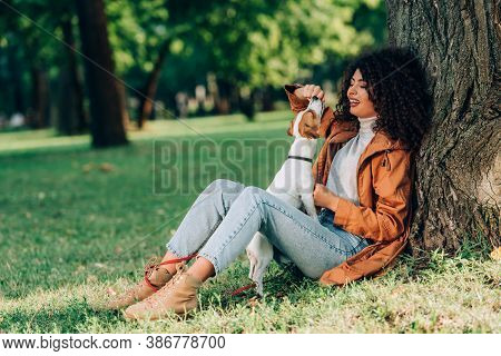 Selective Focus Of Woman In Raincoat Playing With Jack Russell Terrier Near Tree In Park