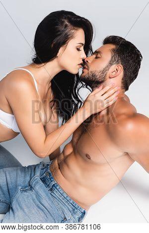 Seductive Woman In Bra Kissing Sexy Man On Grey