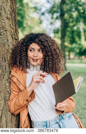 Selective Focus Of Curly Woman In Raincoat Looking Away While Holding Pen And Notebook In Park