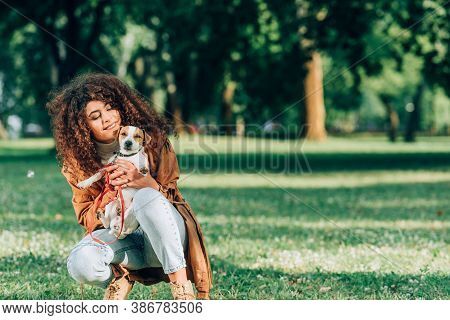 Curly Woman In Raincoat Hugging Jack Russell Terrier On Lawn In Park