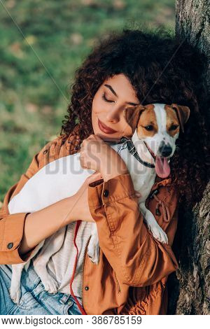 Young Woman In Raincoat Hugging Jack Russell Terrier Near Tree