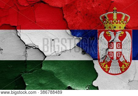 Flags Of Hungary And Serbia Painted On Cracked Wall