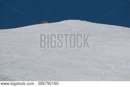 Snowboarder Tracks Lead Down The Mountain Side From A Deserted Summit