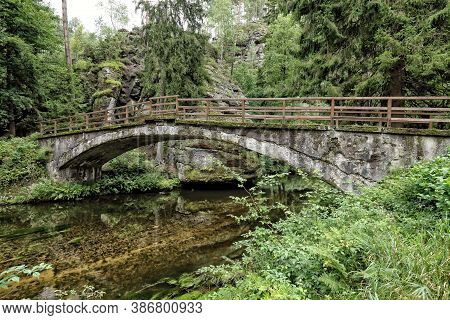 Old Stony Bridge With Wooden Railing Over The Clean River