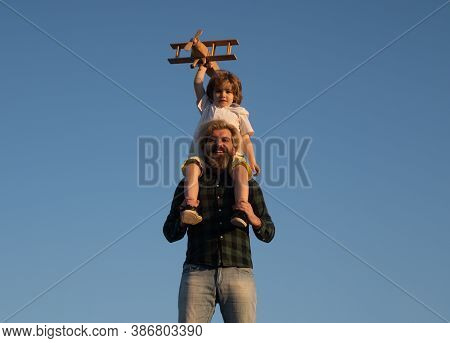 Boy Sitting On Fathers Shoulders. Child Son Pilot And Dad Daddy Father With Airplane