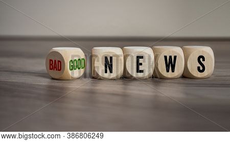 Cubes And Dice With Bad News And Good News On Wooden Background