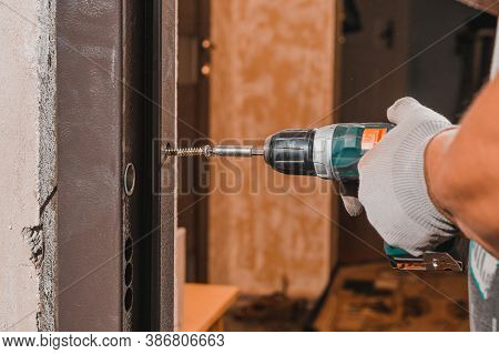 The Carpenter Drills Holes In The Wall And The Metal Door Frame With A Drill, Later Screws The Screw