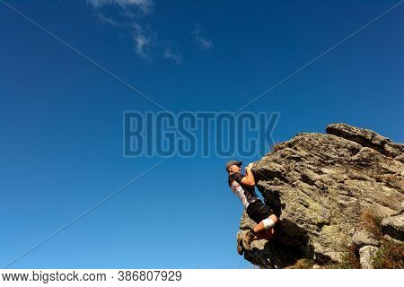The Man Is Engaged In Mountaineering, Climbs To The Top, An Epic View Of The Climber Against The Sky