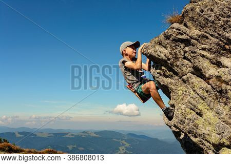 The Boy Is Engaged In Mountaineering, A Child Climbing A Rocky Mountain, A Brave Boy.