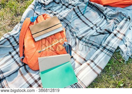 Directly above view of orange satchel and workbooks on gray blanket, picnic after school concept
