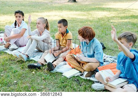 Group of multi-ethnic schoolchildren sitting on blanket in park and raising hands while answering teachers question