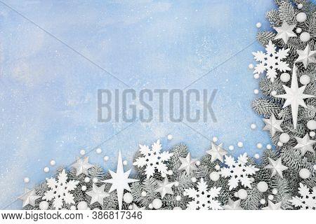 Festive Christmas snow covered fir border with white star, snowflake & ball bauble decorations on pastel blue background. Xmas & winter theme for the holiday season. Top view, flat lay, copy space.