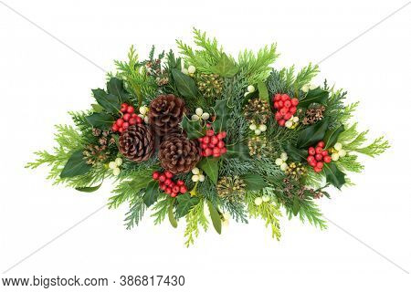 Christmas winter & New Year decorative display with holly, ivy, mistletoe, cedar cypress leaves & pine cones on white background. Xmas composition of traditional flora. Flat lay, top view, copy space.