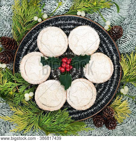 Traditional Christmas mince pies on a plate with winter berry holly & icing sugar dusting, snow covered fir, cedar leaves, mistletoe & pine cones. Festive food composition. Flat lay, top view.