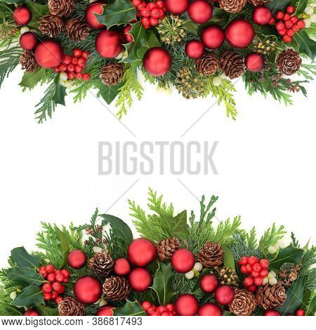 Christmas festive background border with red bauble decorations & natural winter greenery of holly, ivy, mistletoe, pine cones & cedar leaves. Composition for the Xmas season & New Year. Copy space.