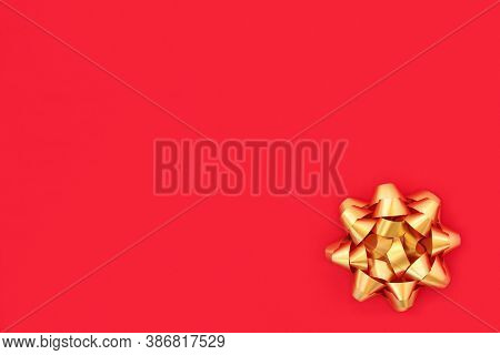 Christmas gold ribbon bow on red wrapping paper background. Minimal design symbol for the festive Xmas season, birthdays & Valentines.
