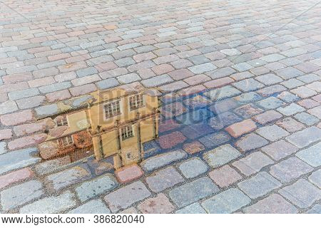 Reflection Of An Ancient House In A Little Pond On A Cobbled City Square After A Rain Shower