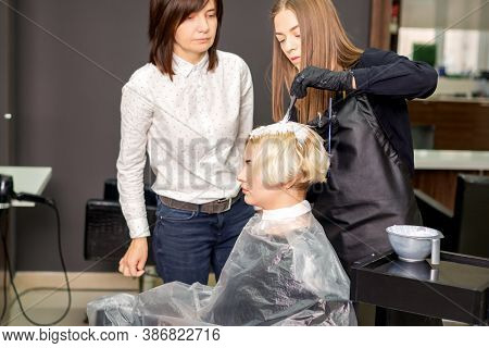 Young Female Trainee Learns To Draw Womens Hair Under The Supervision Of A Professional Hairdresser