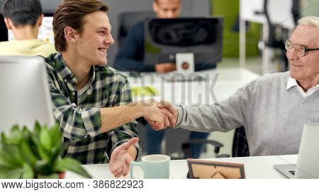 Aged Man, Senior Intern Smiling At His Young Colleague, Shaking Hands, Friendly Male Worker Cheering
