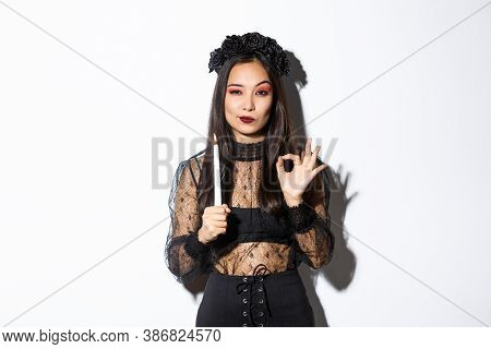 Image Of Young Witch Assuring You In Something, Holding Lit Candle And Showing Okay Gesture. Concept