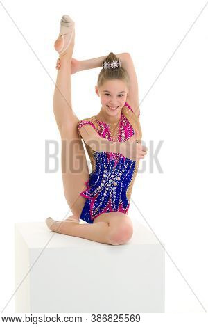 Elegant Little Girl Gymnast In A Sports Leotard. She Performs A Gymnastic Element On A White Cube. T