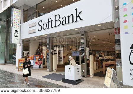 Tokyo, Japan - December 1, 2016: Person Walks By Softbank Mobile Phone Network Shop In Tokyo, Japan.