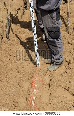 Worker Installing Sewer Pipe In Sandy Trench
