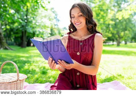 leisure and people concept - happy smiling woman with picnic basket and food sitting on blanket and reading book at summer park