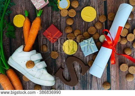 Dutch Holiday Sinterklaas Background With Children Shoe, Carrots For Santas Horse, Gifts, Traditiona