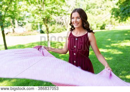 leisure and people concept - happy smiling woman spreading picnic blanket at summer park