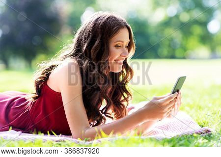leisure and people concept - happy smiling woman with smartphone lying on picnic blanket at summer park