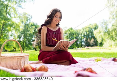leisure and people concept - happy smiling woman with picnic basket and food sitting on blanket and writing to diary at summer park
