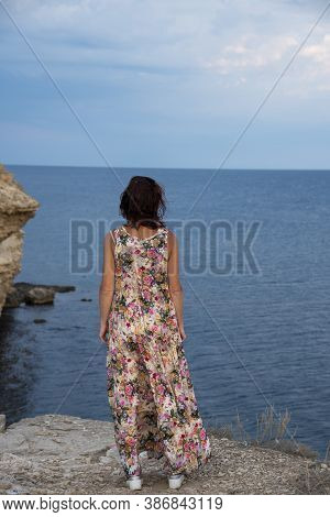 A Woman In A Bright Long Summer Sundress Stands With Her Back To The Camera Against The Backdrop Of