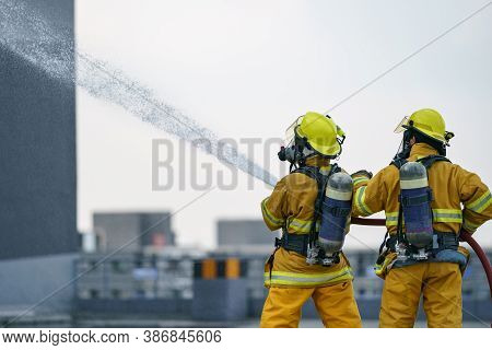 Firefighter Or Fireman Team Work Water Spray By High Pressure Nozzle To Fire.
