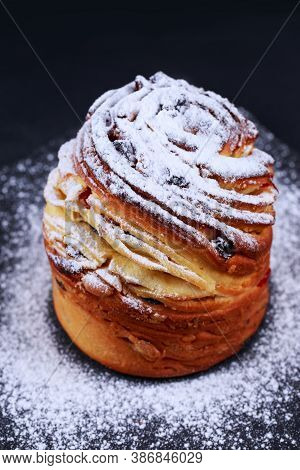 Large Kraffin With Raisins And Powdered Sugar On A Gray Background