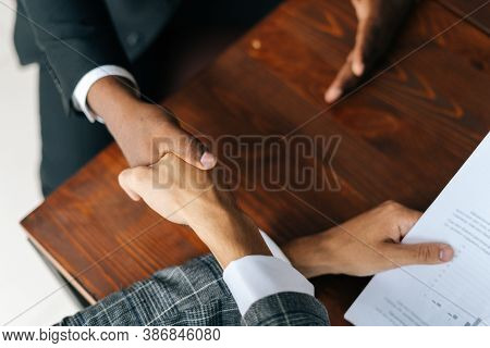 Close-up View Of Handshaking Of Black And White Man Hands After Signing Of Successful Business Contr