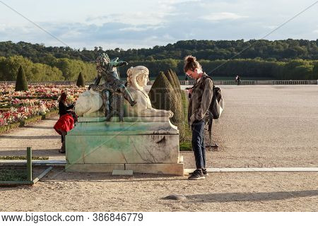 Versailles, France - September 8, 2019: An Unidentified Young Man Is Infatuated With His Smartphone,