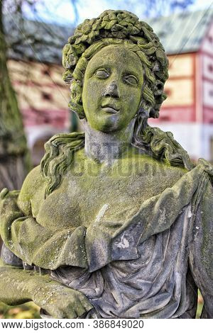 Detail Of Old  Green Moss Covered Statue Of The Girl With Flowers Wreath On Her Head