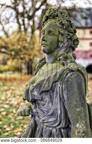 Side Detail Of Old  Green Moss Covered Statue Of The Girl With Flowers In Autumn
