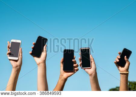 Teens hands holding mobile phones and raising them up against a sky. Group of young people showing smart phone outdoor. Guys and girls holding smartphones with blank and empty screen with copy space.