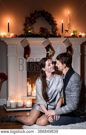 A Warm Picture Of A Married Couple In Love, Christmas Like Fireplace Behind Them. Young Couple Sitti