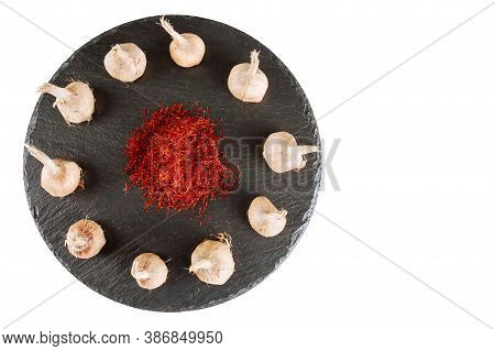Saffron Sativus Bulb And Dry Of Saffron On A Black Board On White Background. Red Stamen Of Saffron.