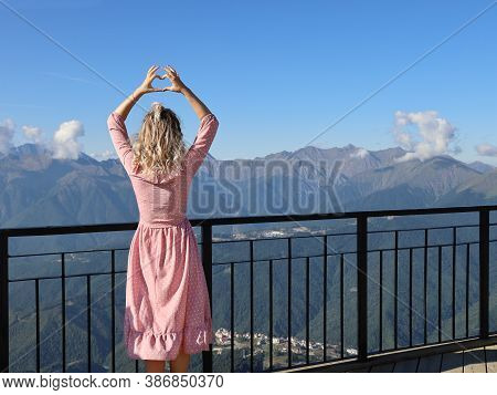 Young Woman In Pink Dress And Blond, Curly Hair Stands With Her Back Near The Railing Of The Observa