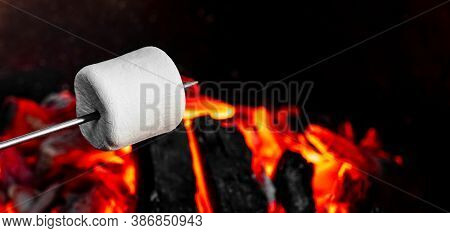 Marshmallow On A Stick Being Roasted Over A Camping Fire. Cooking White Marshmallows On Red Coals In