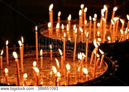 Plenty Of Fired Orange Church Candles On The Rounded Plates With Melted Wax